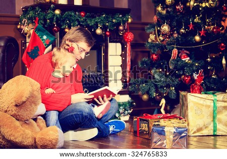 father and little daughter reading book in christmas home - stock photo