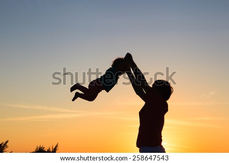Father and little daughter silhouettes playing at sunset - stock photo
