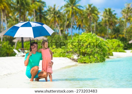 Father and little girl with umbrella hiding from sun at beach - stock photo