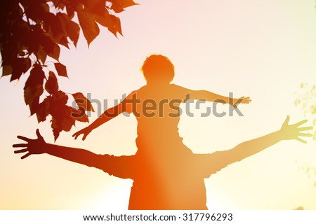 father and little son having fun at sunset sky - stock photo