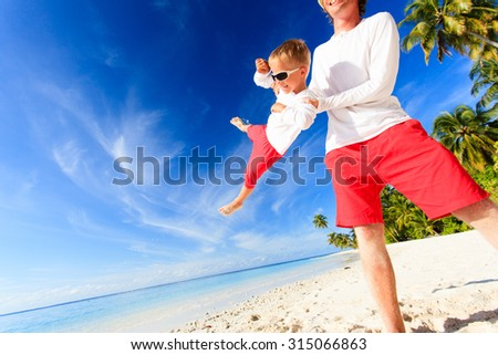 father and little son having fun on summer beach, wide angle - stock photo