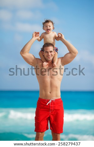 Father and little son having fun on tropical white sand beach near carebbean ocean. Man with little baby boy having fun and playing near the sea water. Ocean.  - stock photo