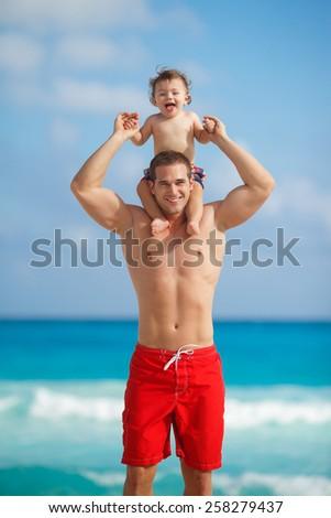 Father and little son having fun on tropical white sand beach near carebbean ocean. Man with little baby boy having fun and playing near the sea water. Ocean.  - stock photo