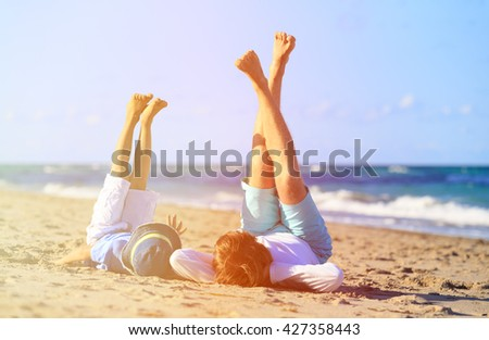 father and little son play on beach - stock photo
