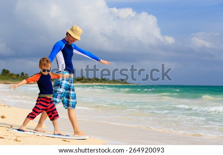 father and little son practicing surfing positin at summer beach - stock photo