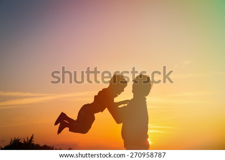 father and little son silhouettes play at sunset - stock photo