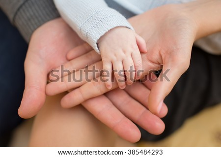 father and mother hold in their hands a little newborn baby's ha - stock photo
