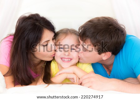 Father and mother kissing your child. Happy family having fun at home - stock photo