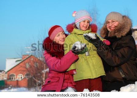 father and mother offer to daughter to make snowball outdoors in winter near house, father and mother sitting - stock photo