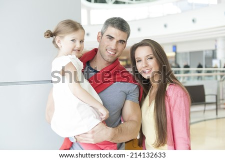 Father and mother pose with young daughter in shopping mall - stock photo