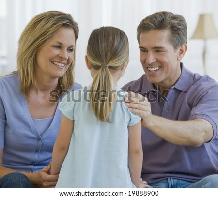 Father and mother smiling at their daughter - stock photo