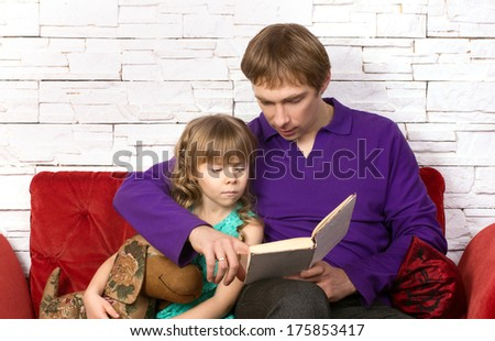 father and preschooler daughter sitting on red sofa on modern background and reading book - stock photo