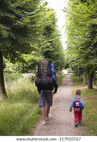 Father and small child with backpacks walking or trekking on a path along a river or canal.  - stock photo