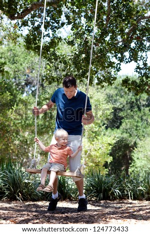 father and smiling happy son on a swing - stock photo