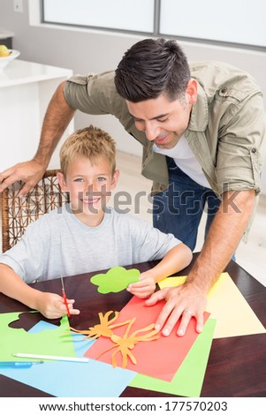 Father and smiling son making paper shapes together at the table at home in kitchen - stock photo