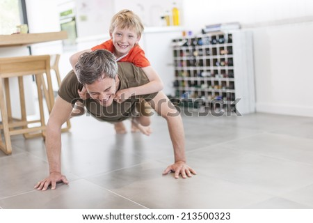 father and son  are doing push ups and having fun  at home - stock photo