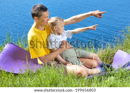 Father and son are playing on the meadow - stock photo