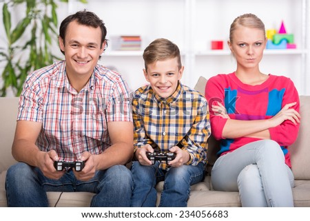 Father and son are playing video game. Mom is boring. - stock photo