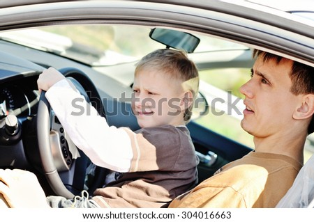 Father and son are  sitting in a car - stock photo