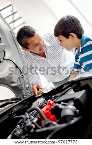 Father and son at the dealer looking at a car engine - stock photo