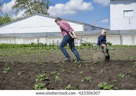 Father and son at the field. Curious little boy helping his father to plant while sitting on plow. Private farm. working together in the garden - stock photo