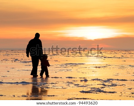 Father and son. Bright solar glow and silhouettes - stock photo