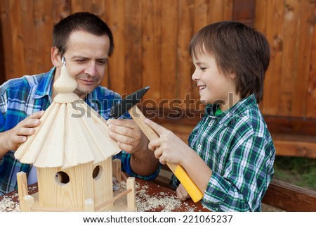 Father and son building a bird feeder together - preparing for winter - stock photo