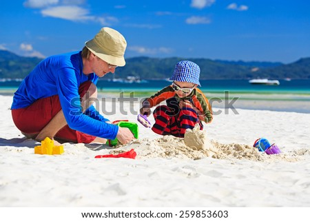father and son building sandcastle on summer beach - stock photo