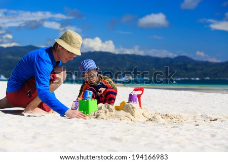 father and son building sandcastle on the beach - stock photo