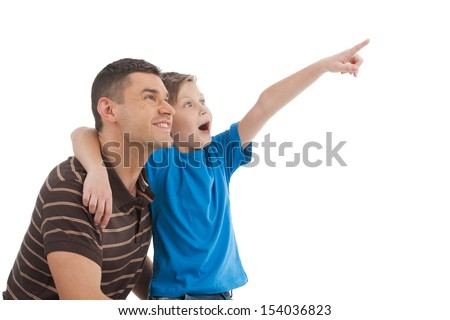 Father and son. Cheerful father and son standing close to each other while child pointing away - stock photo