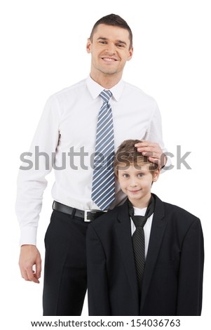 Father and son. Cheerful father in formalwear and son standing close to each other while isolated on white - stock photo