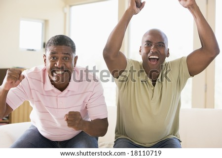 father and son cheering at television - stock photo