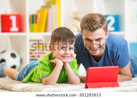 Father and son child playing with digital tablet - stock photo
