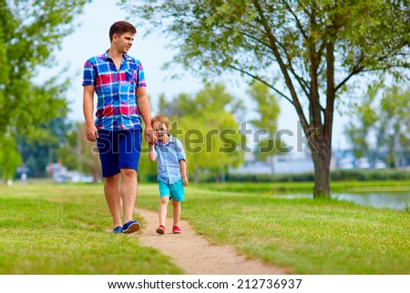 father and son communication, walking outdoors - stock photo