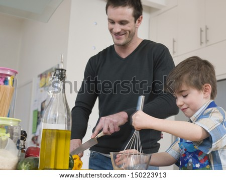 Father and son cooking food together in kitchen - stock photo