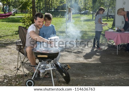 Father and son cooking in front of mobile van - stock photo