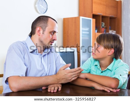 Father and son discussing something serious in living room - stock photo