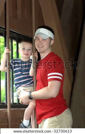 Father and son enjoy visiting the Elizabethton Covered Bridge in Tennessee.  They are standing besides a window inside the bridge. - stock photo
