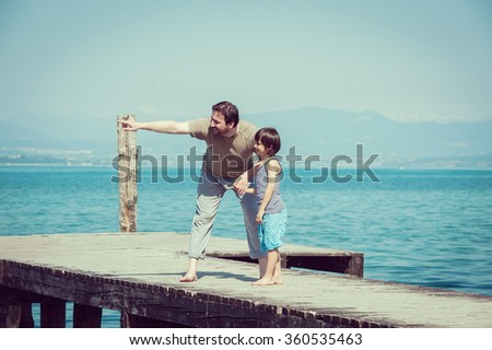Father and son enjoying summer vacation on sea dock - stock photo