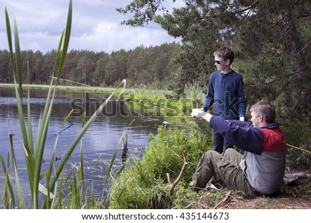 Father and son fishing at lake shore at spring day - stock photo