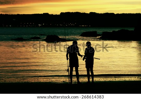 father and son fishing on the beach at dusk  - stock photo