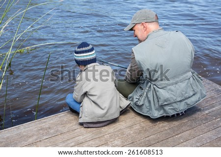 Father and son fishing together in the countryside - stock photo