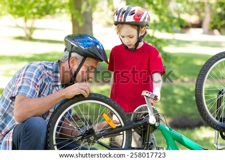 Father and son fixing a bike on a sunny day - stock photo