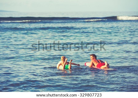 Father and son going surfing together. Summer fun outdoor lifestyle - stock photo