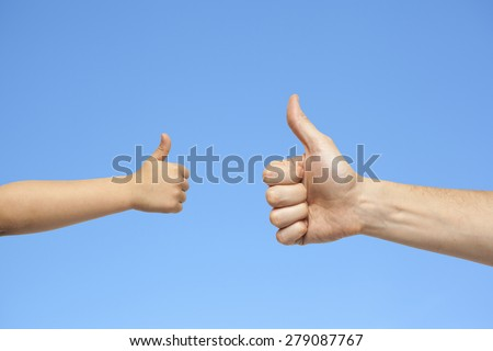 father and son hands giving like on blue sky background - stock photo