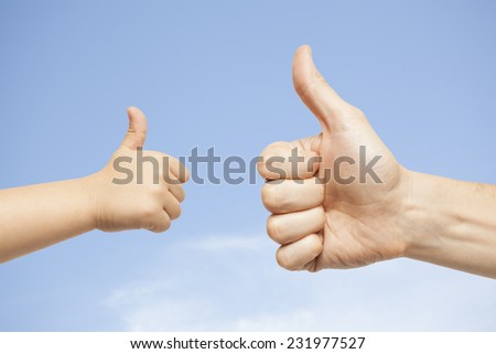 father and son hands giving like on sky background - stock photo