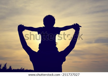 father and son having fun at sunset - stock photo