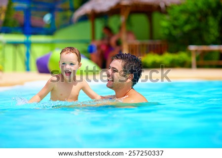 father and son having fun in pool, summer vacation - stock photo