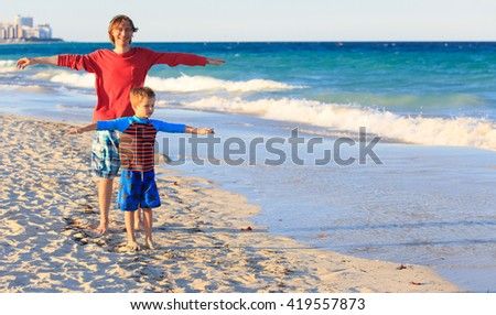 father and son having fun on sea vacation - stock photo