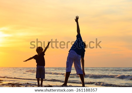 father and son having fun on summer sunset beach - stock photo